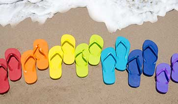 Multi-coloured flip flops on the beach