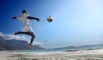 Footballer about to kick a football on the beach
