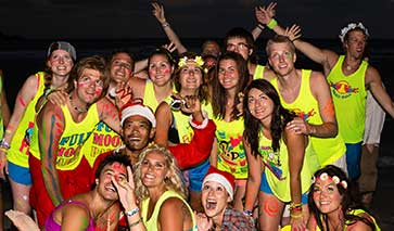 Partygoers at a full moon party in fluorescent colours