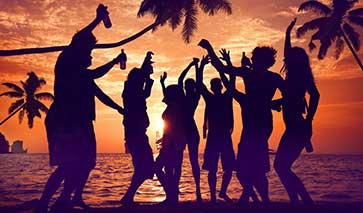 Partygoers at a beach party silhouetted by the setting sun
