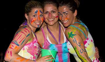 Three women at a party in fluorescent colours