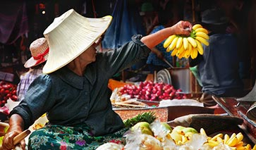 Thailand market place on a river, seller clutching a bunch of bananas