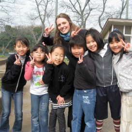 http://i-to-i%20TEFL%20intern%20with%20pupils%20in%20playground%20smiling%20for%20camera