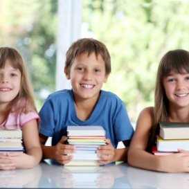 http://3%20young%20TEFL%20students%20with%20books%20smiling%20at%20camera
