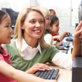http://TEFL%20teacher%20and%20pupil%20working%20with%20a%20computer