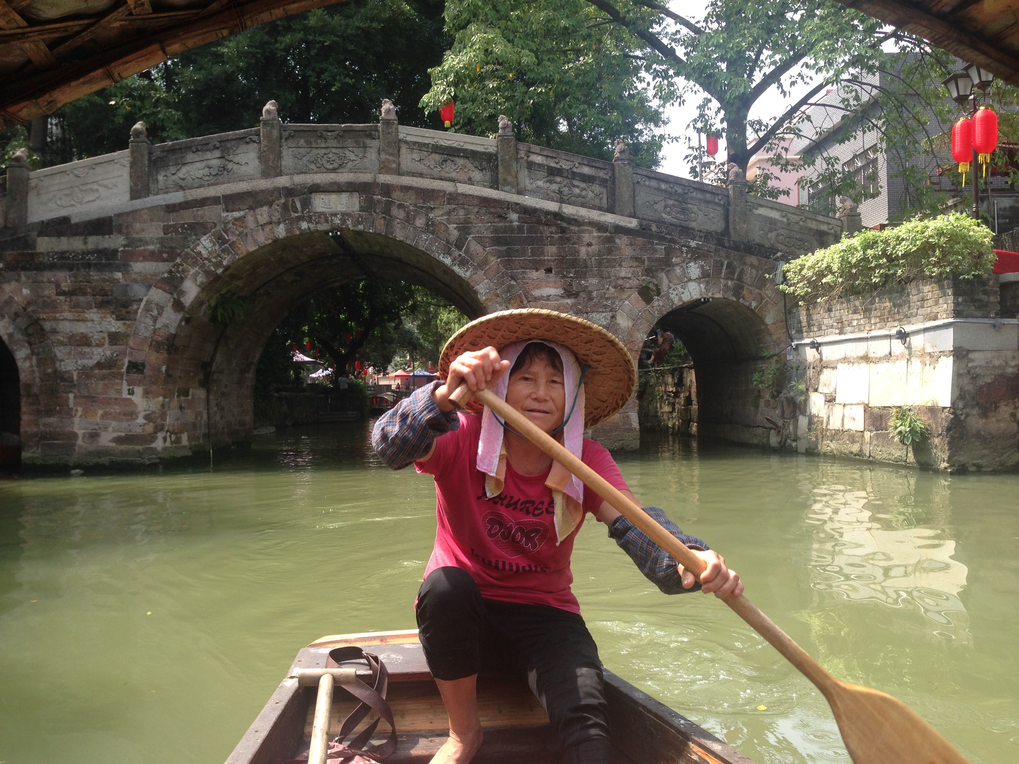 A woman steers her boat at Shun De water village, China