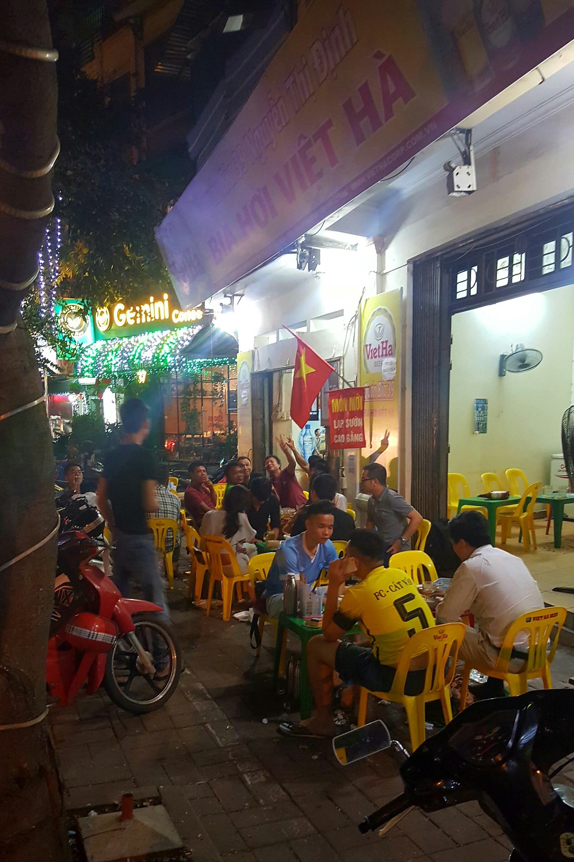 Locals enjoying beer and food at a beer hoi bar in Hanoi, Vietnam