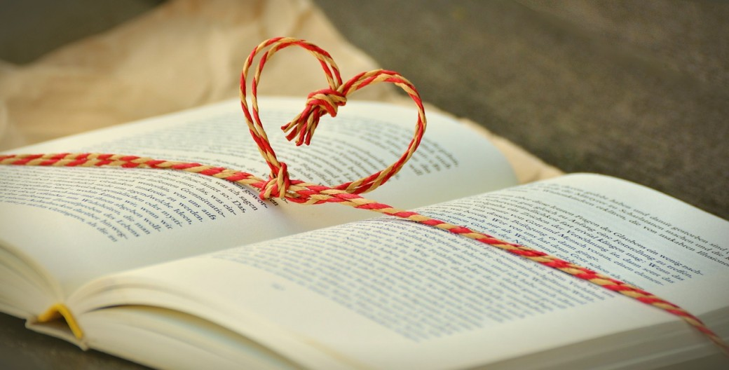 Open book with a string tied around it in the shape of a heart