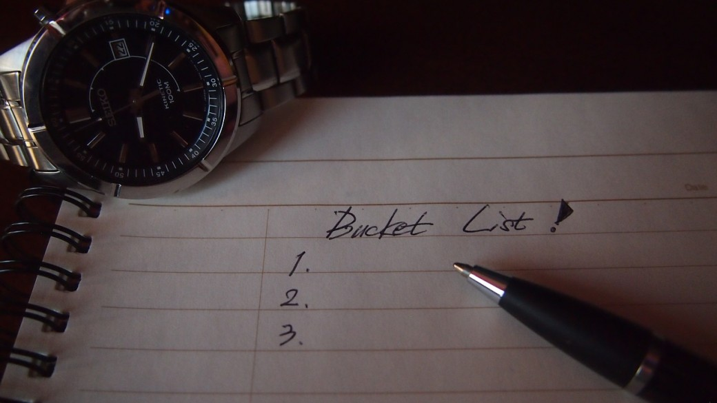 paper with pen and a watch witht he word bucket-list written down