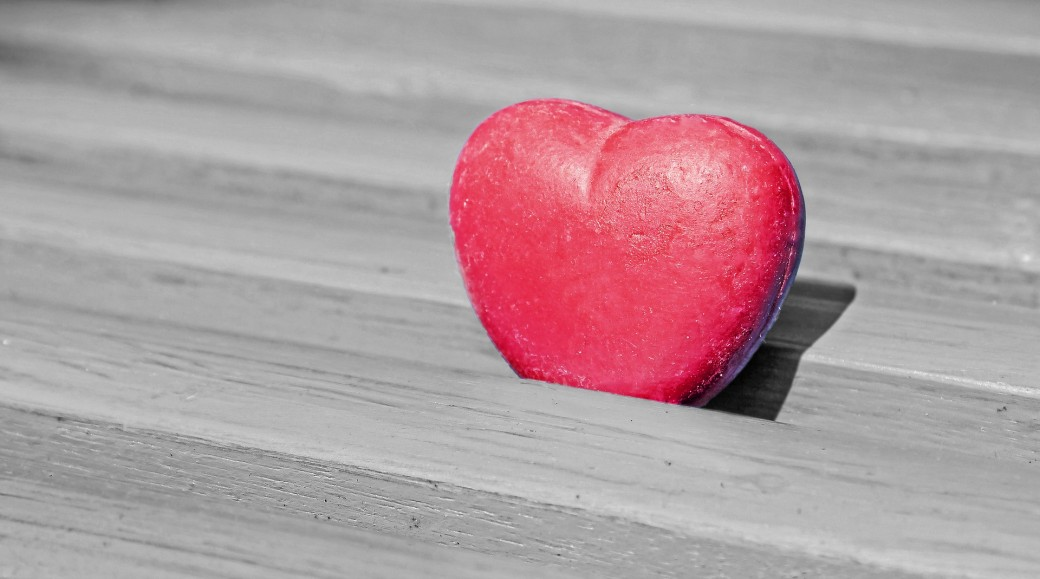 Plastic heart on a wooden bench