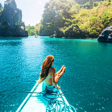 girl sat on a boat on bright blue sea