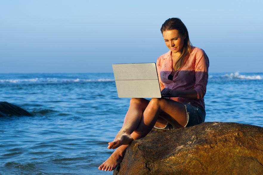 Woman on rock, working on laptop
