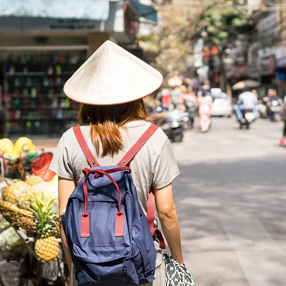 girl with Vietnamese hat walking on street in vietnam
