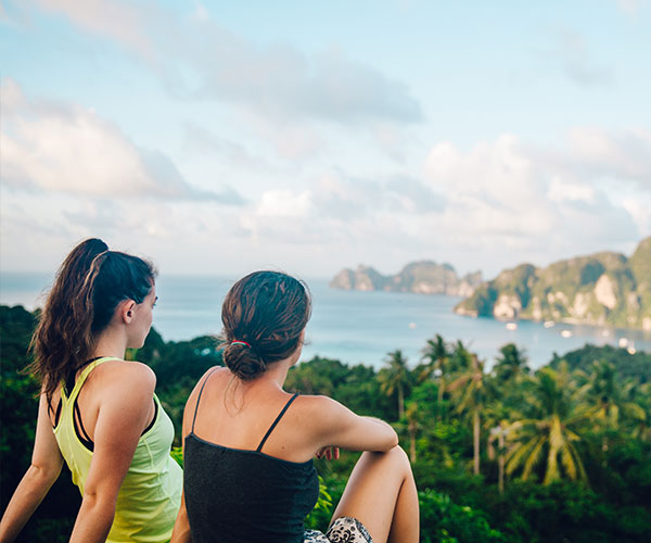 two girls looking out over rain forest