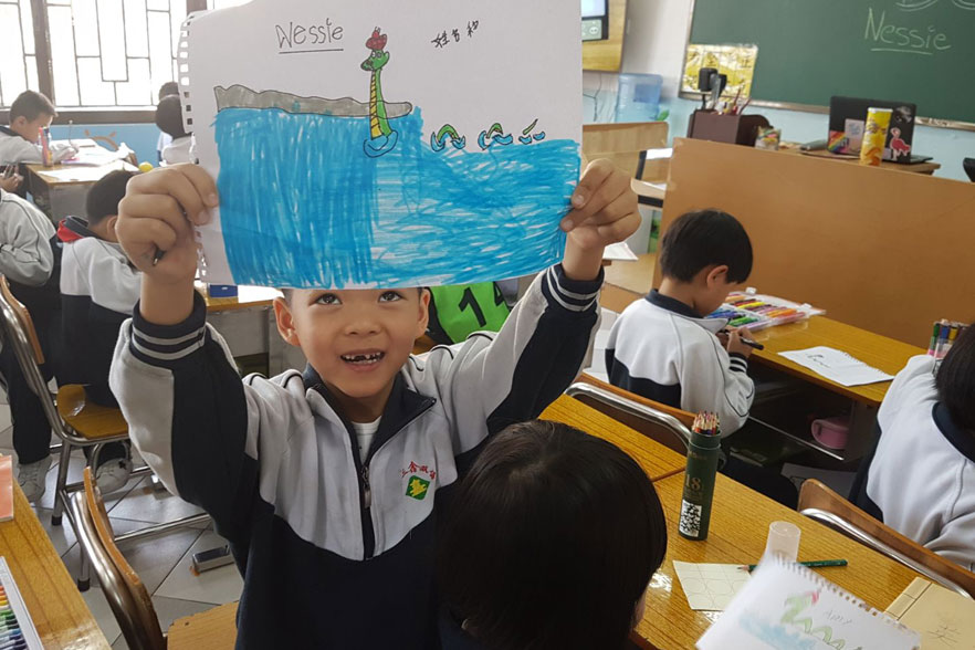 chinese student with drawing of the lock ness monster