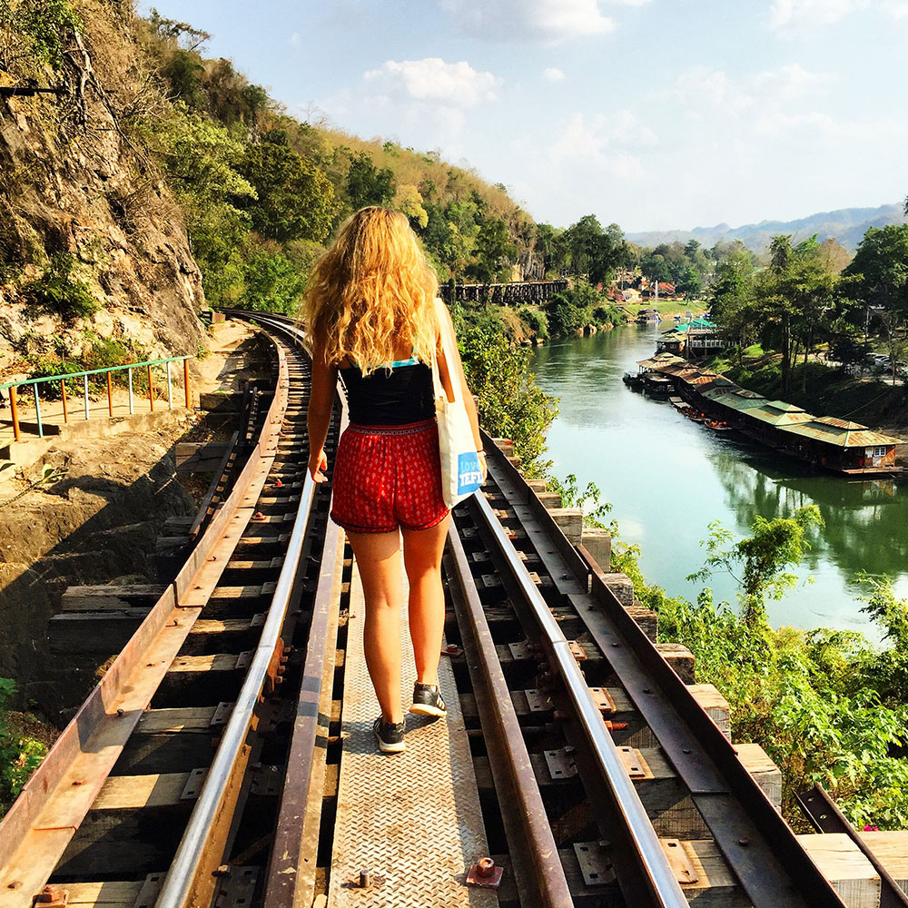 girl walking on rail in thailand