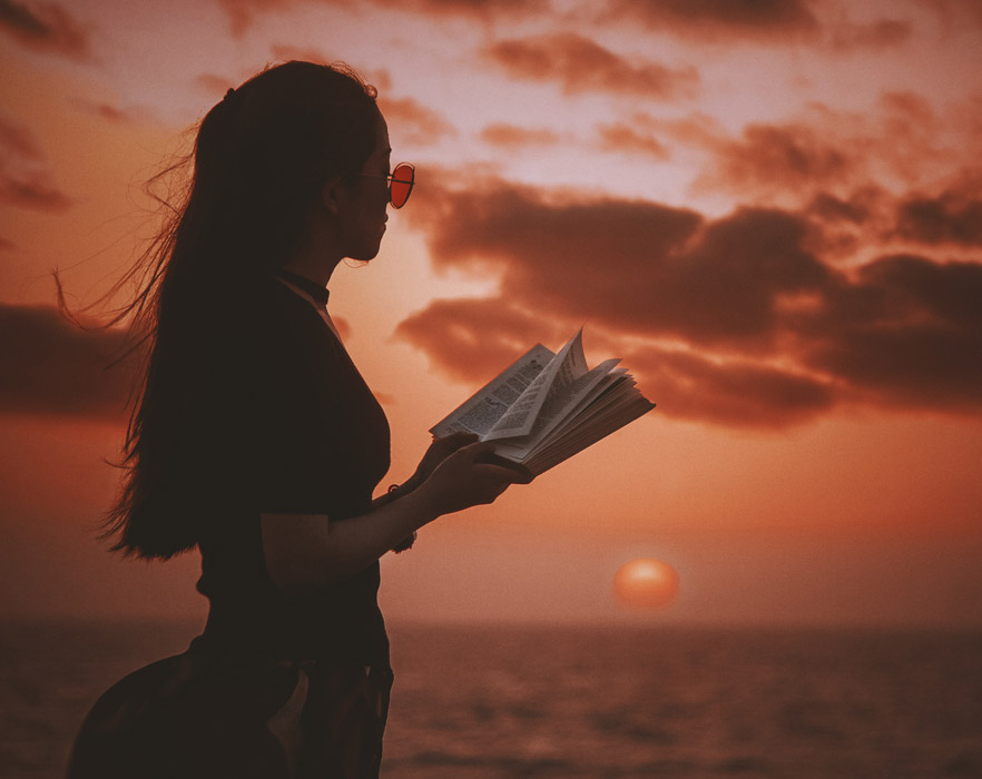 Girl with book at sunset