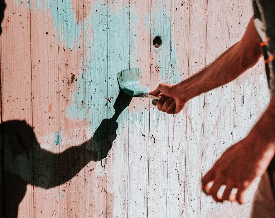 man volunteering to paint fence