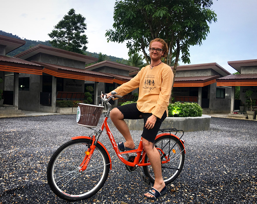 Teacher on bike in front of on-campus houses, Thailand