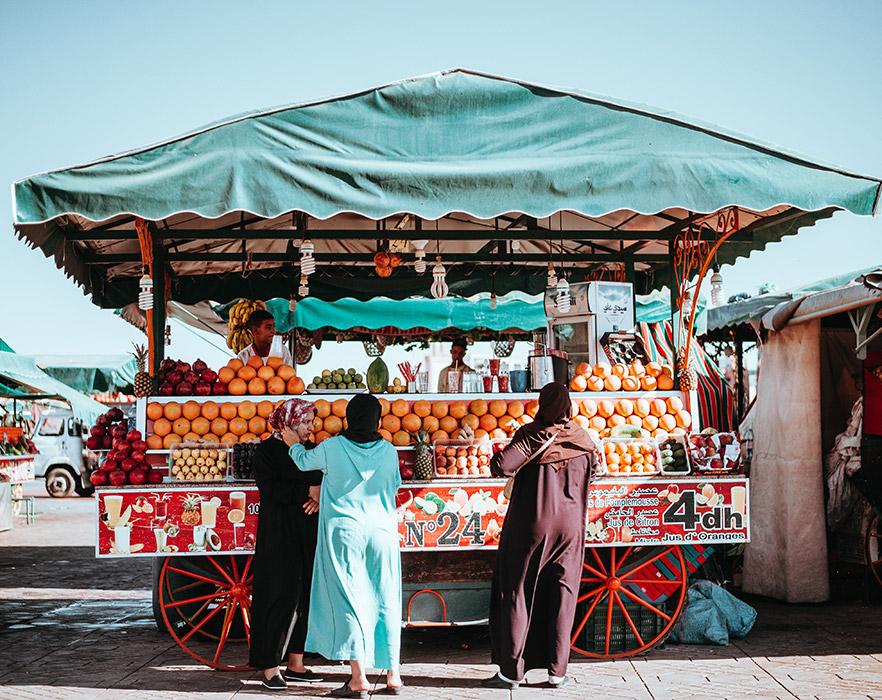 3 women in front of fruit cart