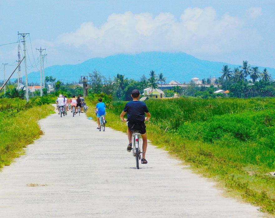 People cycling towards mountain - Vietnam