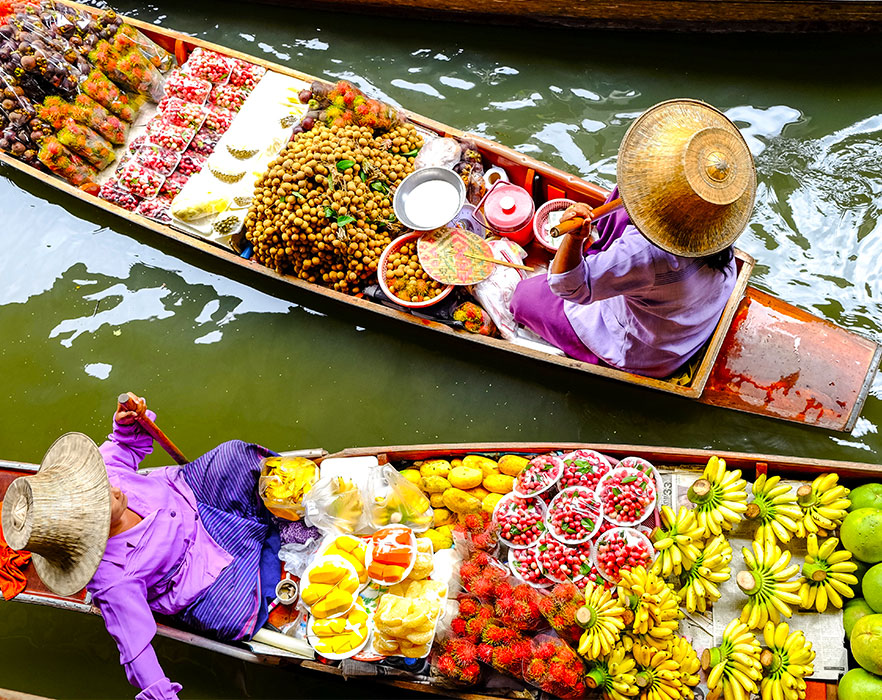 Women in boats with local food