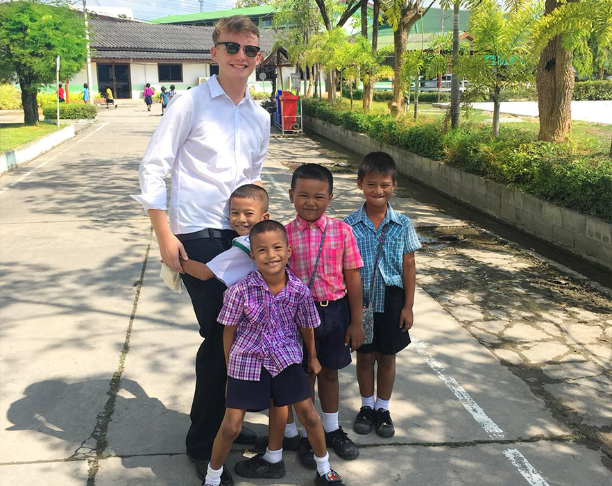 Young TEFL teacher outside with students