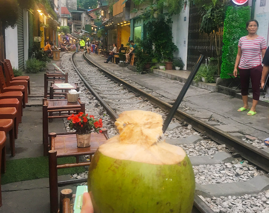 Drinking out of coconuts on Train Street, Hanoi