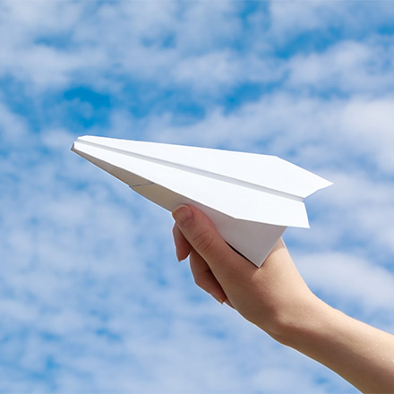 Girl launching paper plane