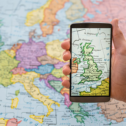 Hand holidng phone with a map of UK over a map of Europe