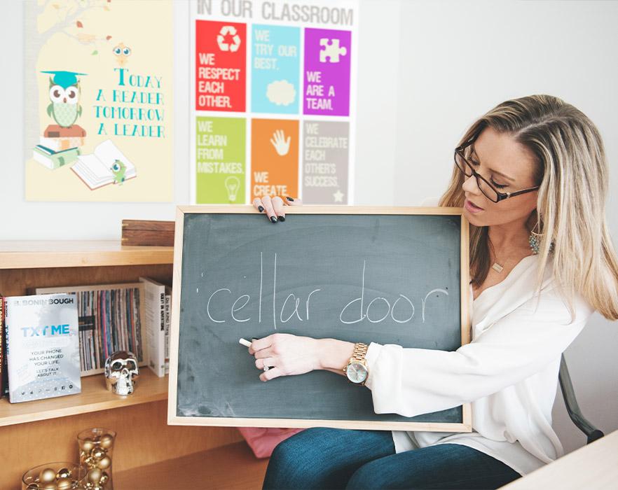 TEFL teacher holding up chalk board