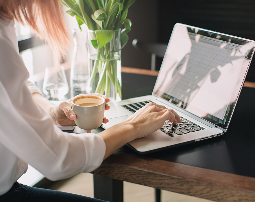 Woman using laptop with coffee in hand