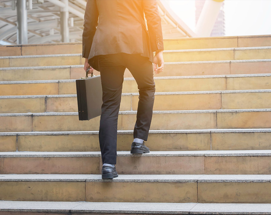 Man walking up steps with briefcase in hand