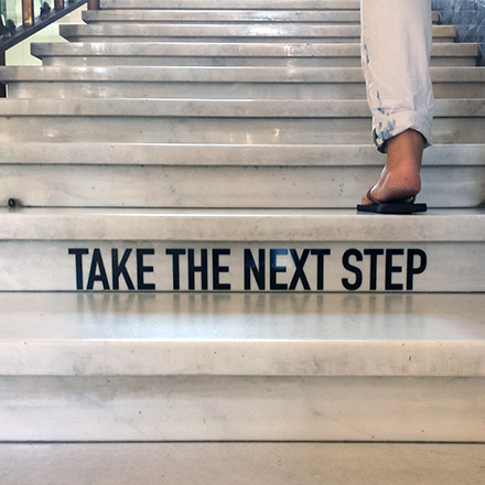 Take the next step sign on stairs
