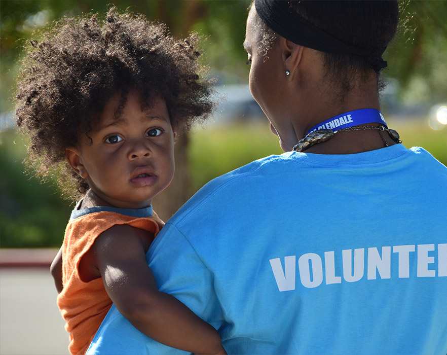 Woman with volunteer top on holding a young child