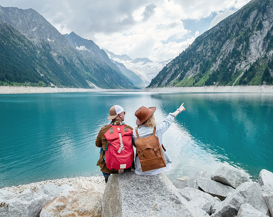 2 people sat in front of lake and mountains