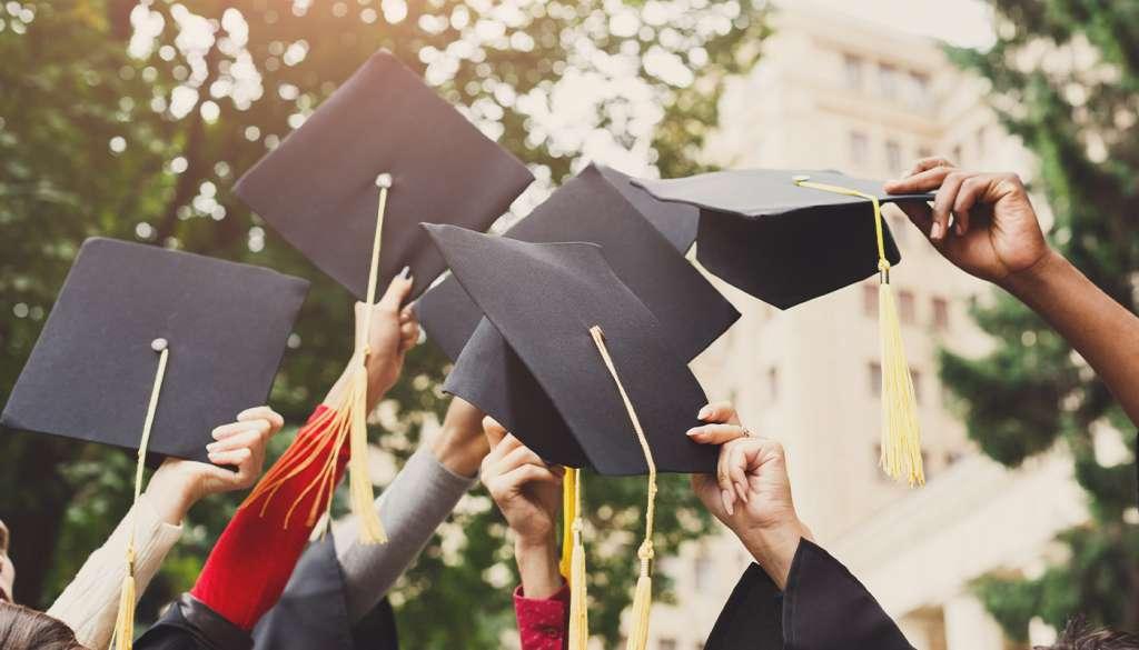 A group of graduates throwing graduations caps