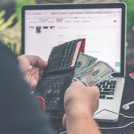 Man holding wallet with money in front of laptop