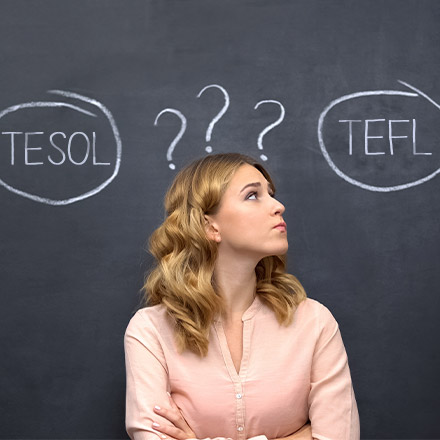Woman stood in front of chalk board with TEFL and TESOL wrote on it