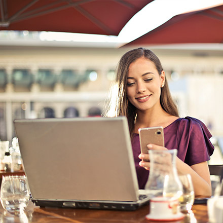 Woman using phone and laptop at outdoor cafe