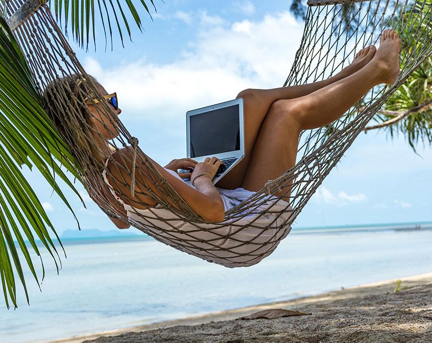 Woman using laptop in hammock on beach