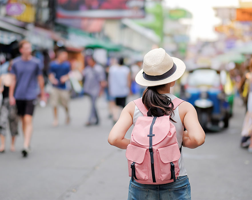 Woman walking through street with backpack
