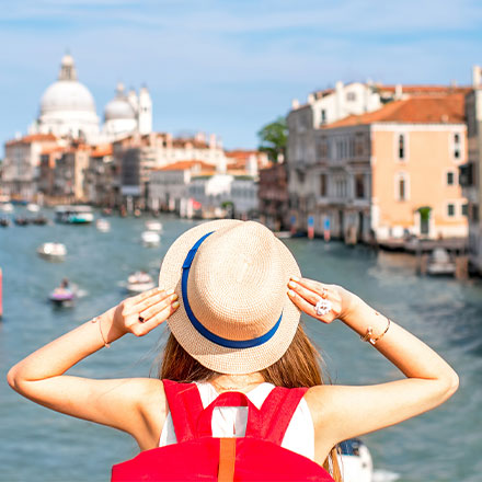 Woman with hat on looking over Grand canal, Venice
