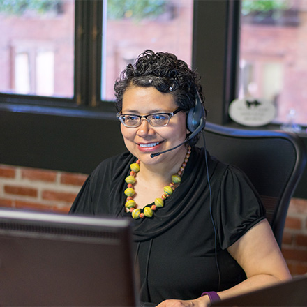 Woman wearing headset taking calls at work
