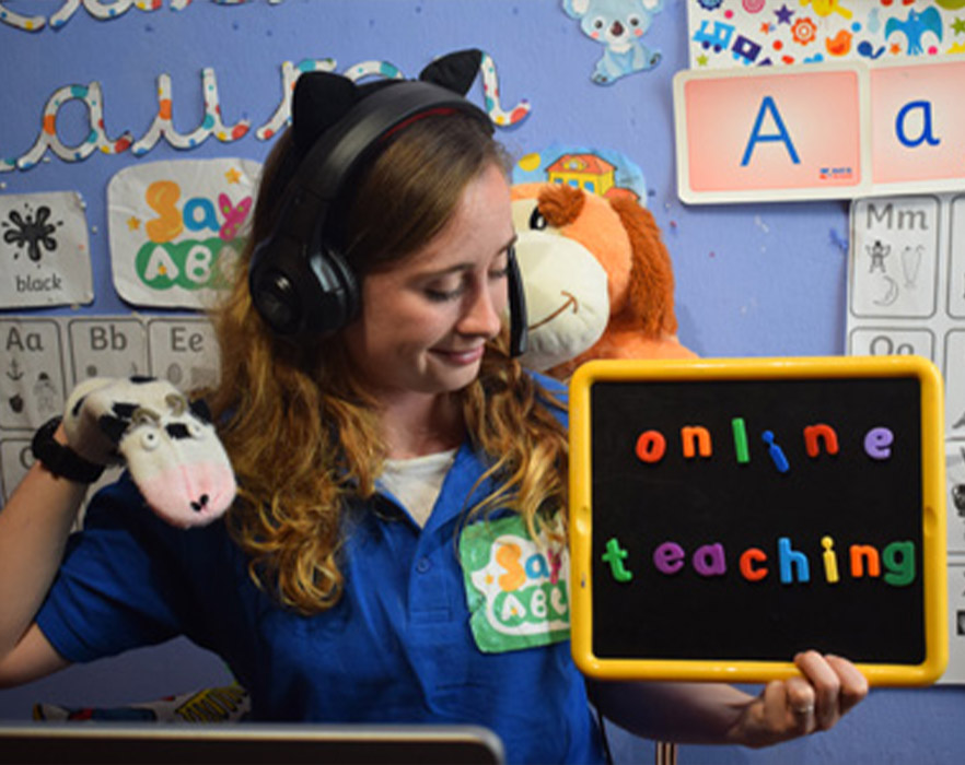Online teacher holding up puppet and props