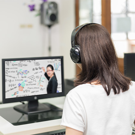 Woman sat at desk having online English lesson on pc