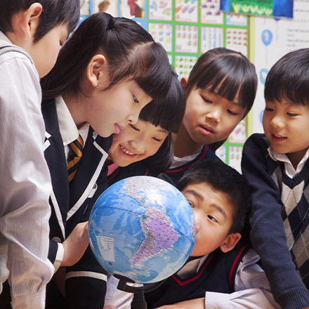 Young students looking at a globe