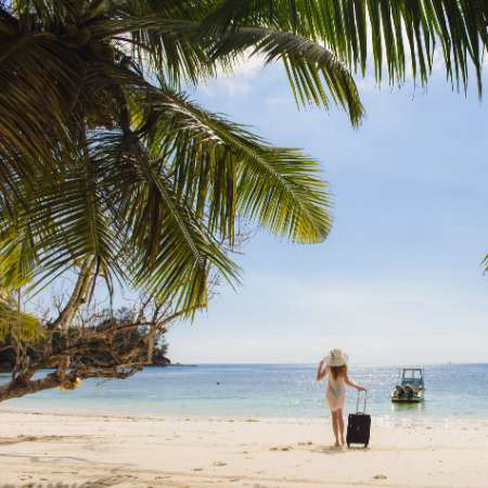 Woman on beach in Thailand with her suitcase