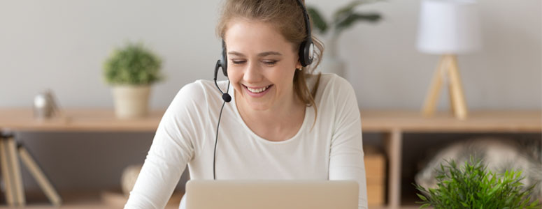 happy girl with a headset talking to someone on the laptop