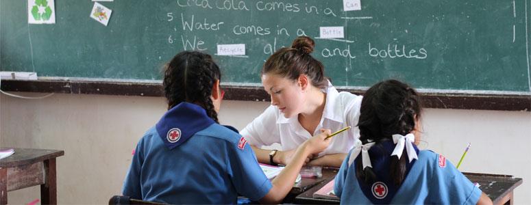 teacher teaching two thai girls in a school
